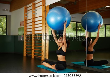 Young athletic woman holding up balance ball and sitting on the mat during her fitness training in gym - stock photo