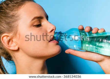 young athletic woman in fitness equipment drinking a bottle of water, on blue background