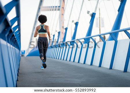 Young athletic woman jogger running on city bridge, rear shot.