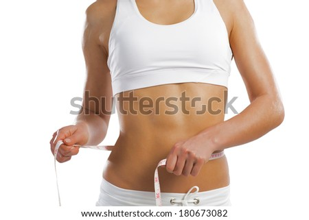 young athletic woman measuring waist, isolated on white background - stock photo