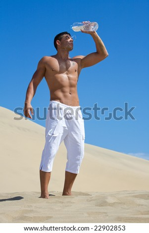 young atlethic man refreshing with water on desert dune - stock photo