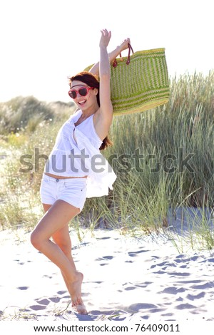 Young atractive woman is dancing with  bag on the beatch - stock photo