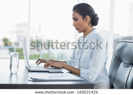 Young attentively working businesswoman sitting at her desk in the office - stock photo