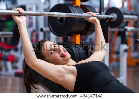 Young, attractive, adorable, cute female athlete working hard, training her chest muscles at the gym with cute but tired face expression.