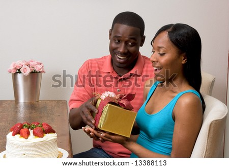 Young attractive african american couple exchanging gifts at their dining table. The couple are looking at each other with broad (and somewhat surprised) smiles. Horizontally framed shot.