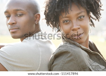 Young attractive african american couple sitting back to back in a city park while on vacation, smiling happy.
