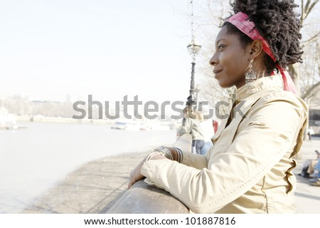 Young attractive african american woman at London's river Thames, smiling.