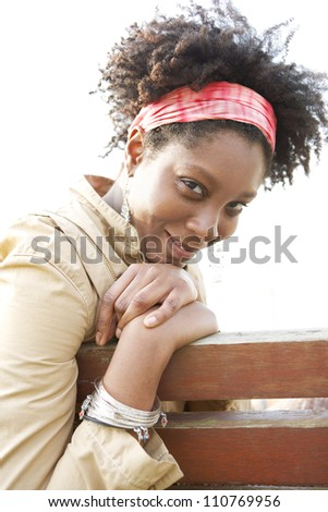 Young attractive african american woman smiling while sitting on a bench in a city park. - stock photo