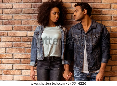 Young attractive Afro-American couple looking at each other while standing against brick wall