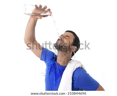 young attractive and athletic sport man exhausted all wet drinking water and pouring bottle on his face refreshing after hard training  isolated on white background - stock photo
