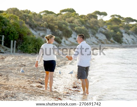 young attractive and beautiful American couple in love walking on the beach the man holding woman hand with barefoot on the wet sand smiling happy in romantic summer holidays - stock photo