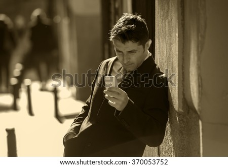 young attractive and busy businessman with blue eyes wearing suit and tie using mobile phone sending message or consulting internet leaning on street wall outdoors in the morning in black and white - stock photo