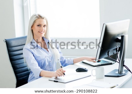Young, attractive and confident woman working in office. Retoucher editing photos. - stock photo