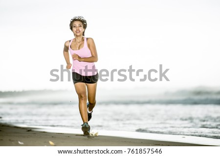 young attractive and fit Asian sport runner woman running on beach