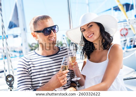 Young, attractive and rich couple have a party on a luxury boat - stock photo