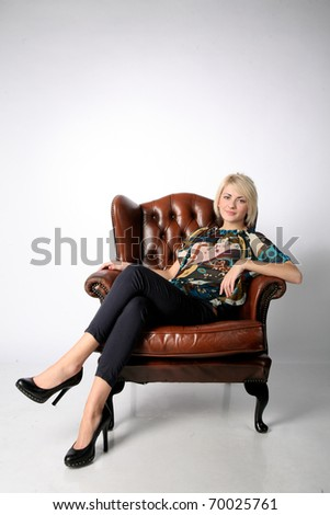 Young attractive and sexy blond female sitting on a chair - stock photo