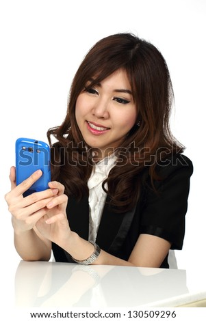 Young attractive Asian businesswoman sitting using mobile phone, isolated on white background.