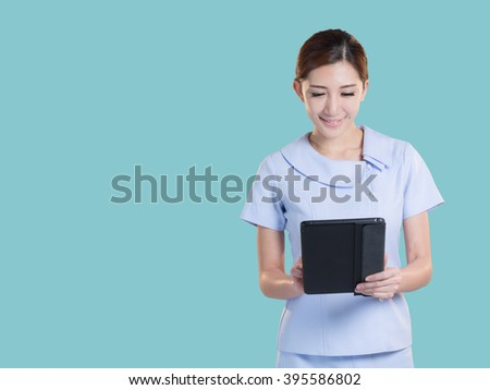 Young attractive asian nurse with pastel green background color.