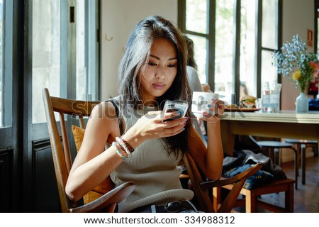 young attractive Asian student typing a message on her smart-phone in a coffee-shop. She is holding a cup of tea - stock photo