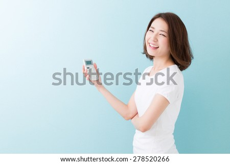 young attractive asian woman having an electronic calculator - stock photo