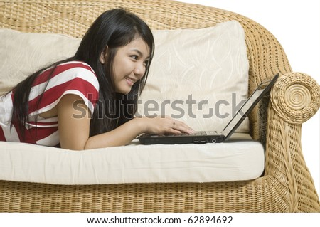 Young attractive Asian woman laying on sofa with computer