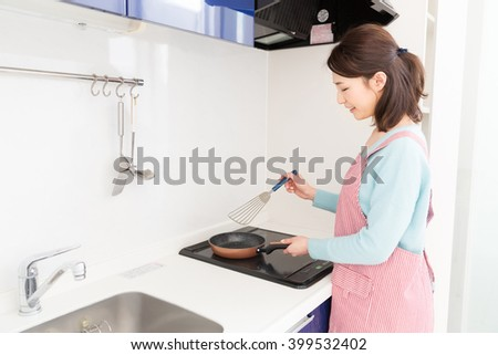 young attractive asian woman who cooks in a kitchen