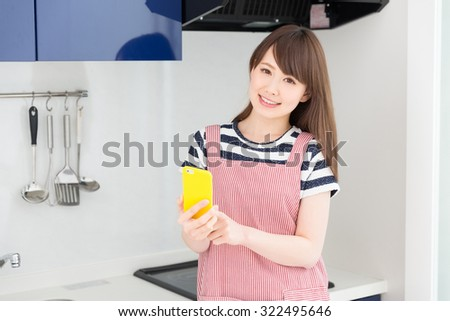 young attractive asian woman who cooks while watching a smart phone