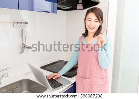 young attractive asian woman who cooks while watching Laptop
