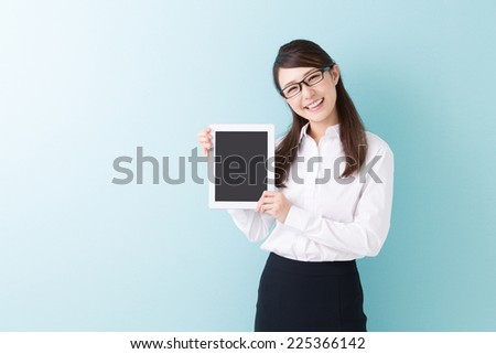 young attractive asian woman who shows a tablet - stock photo