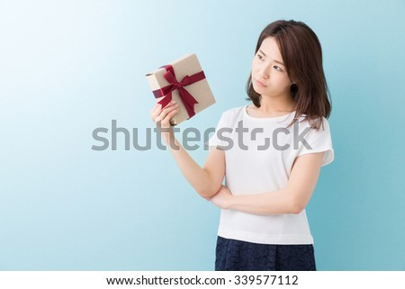 young attractive asian woman who thinks while having a present - stock photo