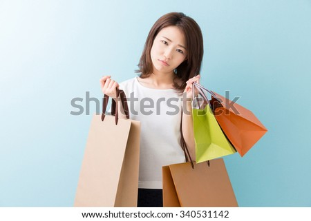 young attractive asian woman who thinks while having shopping bags - stock photo