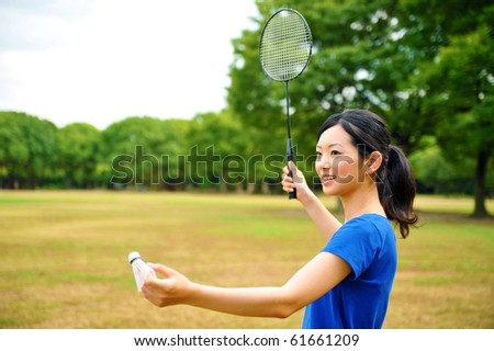 young attractive asian woman with badminton in the park