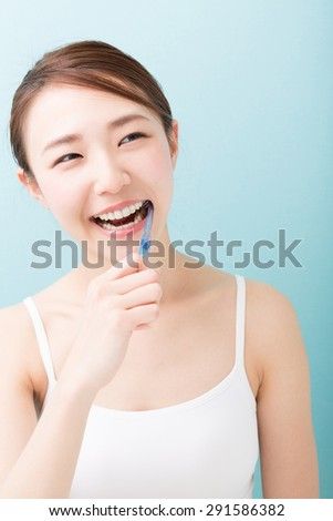 young attractive asian woman with healthy teeth holding a tooth brush - stock photo