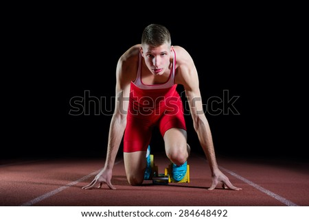 Young attractive athlete on the starting block - stock photo