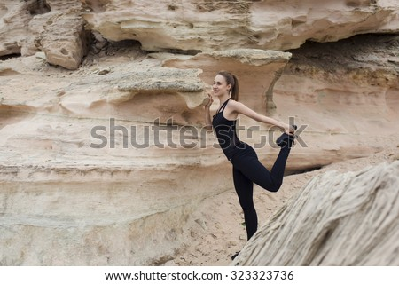 Young attractive athletic female with a beautiful slender figure stretching leg muscles before began her morning run in natural park, fit woman with perfect body working outdoors, copy space area - stock photo