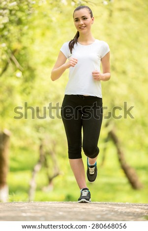 Young attractive athletic girl jogging at park in the morning.
