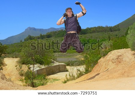 Young attractive backpacker jumps while talking over phone - and misty mountain landscape as background. Shot in Stellenbosch Mountain, Western Cape, South Africa.