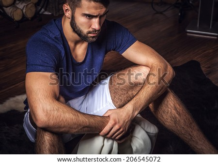 Young attractive bearded men pose in modern room. Close-up photo.  - stock photo