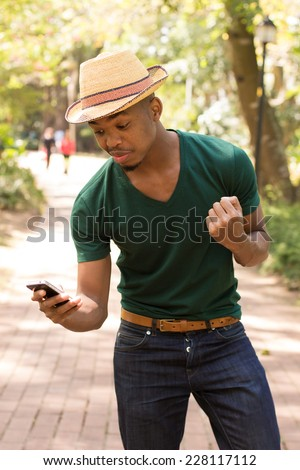 Young Attractive Black man using his cellphone - stock photo