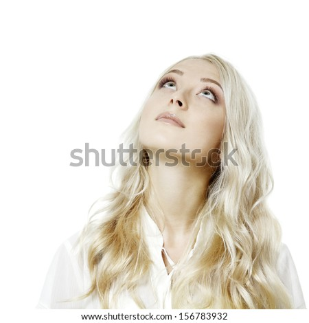 Young attractive blond girl looking up at copy space over white - stock photo