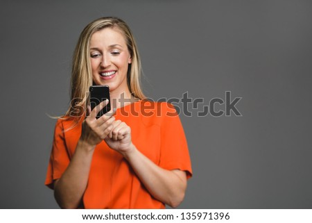 Young attractive blond woman smiling down at her smartphone in her hand. - stock photo