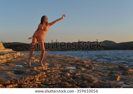 young attractive blonde bikini girl on the rocks near the sea, women posing on sunset time.