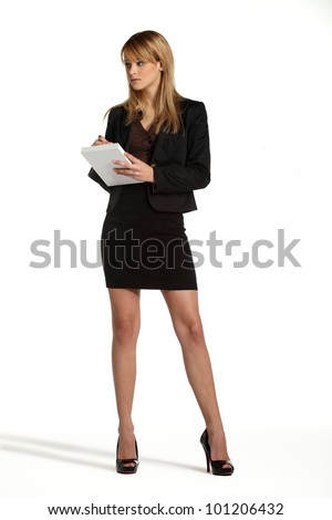 Young attractive blonde business girl standing and taking notes - stock photo