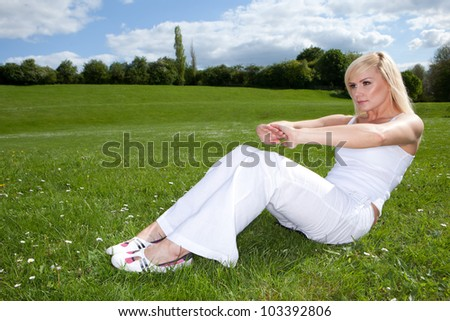 Young attractive blonde exercising outside on a field - stock photo
