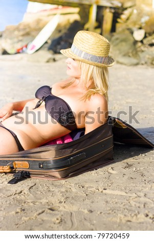 Young Attractive Blonde Female Posed Against Open Suitcase On Beach Looking Out At The Ocean In A Travel Holidays And Vacations Concept - stock photo