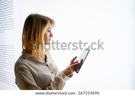 young attractive blonde girl using modern tablet on a light box background - stock photo