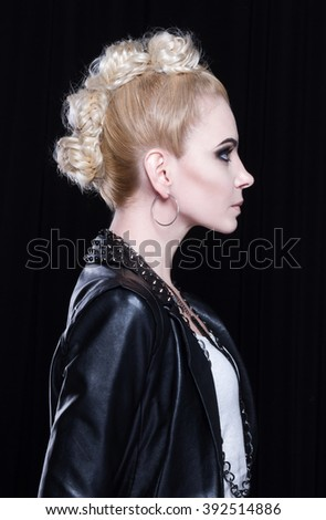 Young attractive blonde in a leather jacket. She is rebellious, she has a creative mohawk and heavy makeup. She wears a lot of metal accessories. Side view. - stock photo