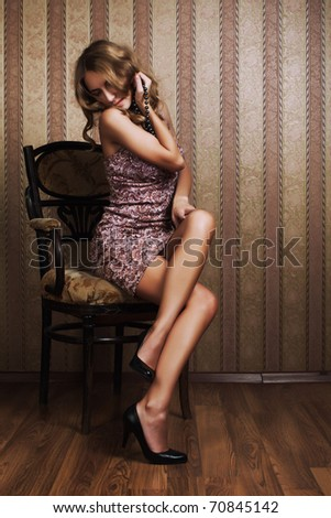 young attractive blonde poses in a luxurious interior - stock photo