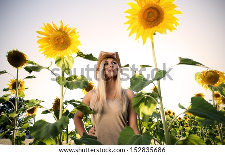 Young attractive blonde wearing hat standing in sunflowers - stock photo