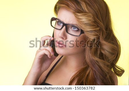 Young attractive blonde woman speaking on mobile phone - stock photo
